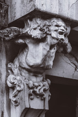 bust of concrete of a terrible woman on the facade of an old house