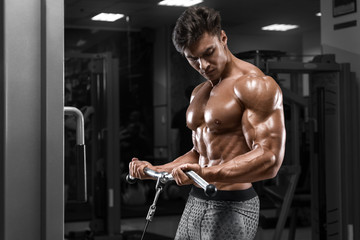 Muscular man working out in gym doing exercisesl at biceps, strong male naked torso abs
