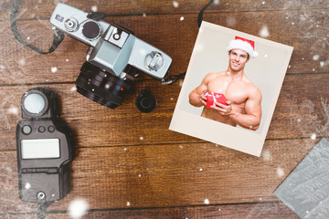 Shirtless macho man in santa hat holding gift against view of an old camera with photo flash