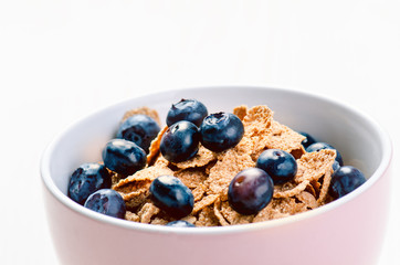 Full muesli bowl on a white table with blueberry. Healthy breakfast cereals with milk, seed, fruit. Oat flakes