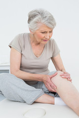 Senior woman with her hands on a painful knee