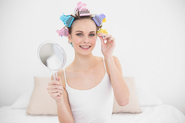 Amused natural brown haired woman in hair curlers plucking her eyebrows