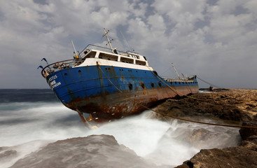 Tourists look at the Togo-registered, 885-tonne bunker tanker Hephaestus, which ran aground last February, in Qawra