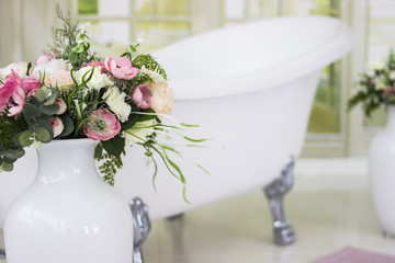 Porcelain freestanding bath in designed white bathroom. White luxurious bath, a bouquet of flowers in a large vase. Still life or compass.