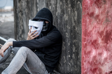 Mystery man wearing hoody jacket taking off the mask showing another mask under it, depression self destruction suicidal addiction massive depressive disorder concept