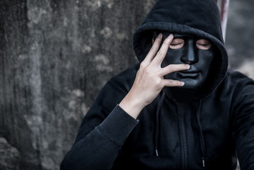 Mystery man in black mask with hoody jacket close his eye thinking of something. feeling stressed or headache gesture