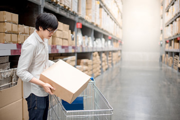 Young Asian man putting paper box into trolley cart in warehouse, shopping warehousing concept