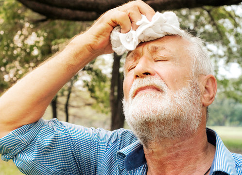 Senior man tired Wiping sweat with a towel in the park, health care concept.