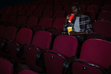 Man having cold drink while watching movie