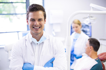 Portrait of dentist standing with arms crossed
