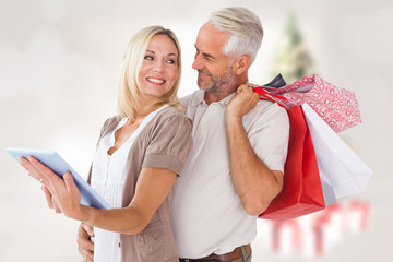 Happy couple with shopping bags and tablet pc against blurry christmas tree in room