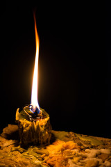 Closeup Flame from Candle with candle drippings in night scene