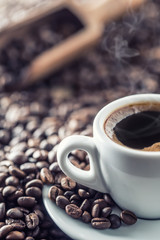 Spoed Fotobehang Cafe Cup of black coffee with beans on wooden table