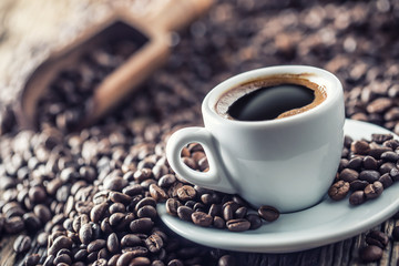 Poster Cafe Cup of black coffee with beans on wooden table
