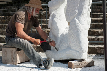 Sculptor at work on marble statue with hammer and chisel