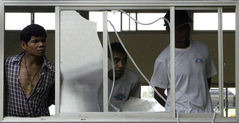 Thai workers look out of a broken window after a riot in southern Taiwan.