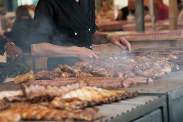 Man grilling an assortment of meat and chiken on a large barbecue