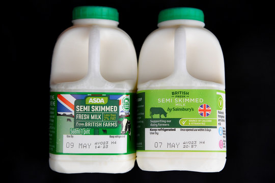 Cartons of milk from Asda and Sainsbury's can be seen in this photo illustration