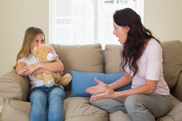 Angry mother shouting at daughter on sofa