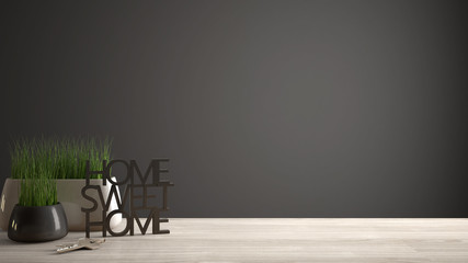 Wooden table, desk or shelf with potted grass plant, house keys and 3D letters making the words home sweet home, gray copy space background