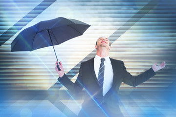 Businessman sheltering under black umbrella testing against window overlooking city