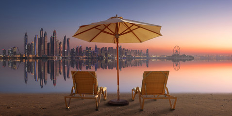 Beautiful terrace with two chairs and an umbrella with Dubai Marina view