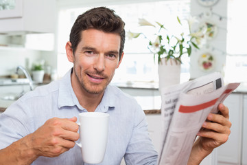 Man with newspaper and coffee cup at home
