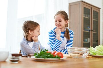 Smiling little girl wearing aprons looking at each other while discussing festive menu for Mothers Day celebration, interior of spacious kitchen on background