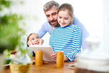 Bearded man and his little daughters gathered together at modern kitchen and studying recipe of delicious dessert with help of digital tablet while thinking over festive menu for Mothers Day.