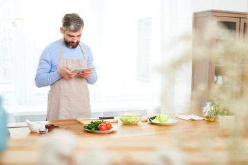 Bearded middle-aged food blogger wearing apron standing at wooden table and photographing ingredients for delicious vegetable salad on digital tablet