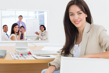 Young businessman presenting figures  against female artist at desk with computer in the office