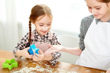 Cute little girl passing cookie cutter to elder sister while preparing delicious present for Mothers Day, close-up shot