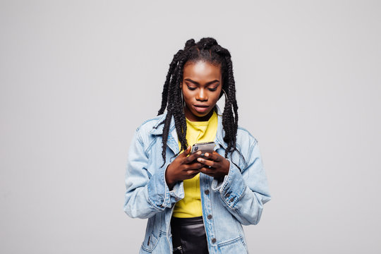 Smiling afro american woman using smartphone over gray background