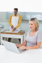 Woman with laptop and man chopping vegetables