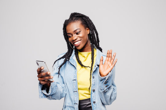 Joyful woman holding mobile phone and smiling on camera while taking selfie isolated over gray background