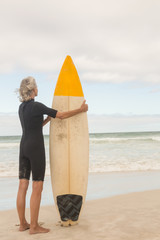 Rear view of woman holding surfboard while standing on shore