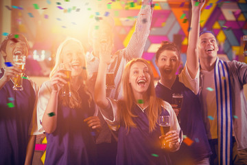Group of friends cheering in party while having glass of champagne against flying colours