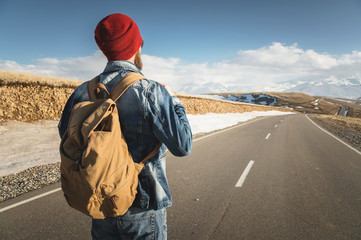 A bearded hipster with an old-fashioned vintage backpack wearing sunglasses with a red hat and jeans jacket and jeans stands on a countryside asphalt mountain road and looks at the snow-capped