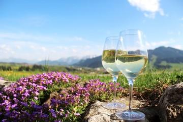Zwei Weißweingläser vor Alpenkulisse, romantisch mit blühendem Blaukissen