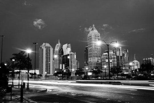 Illuminated Midtown in Atlanta, USA at night. Car traffic, illuminated buildings and dark sky. Black and white