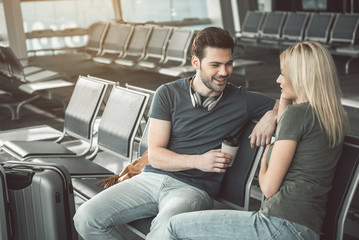 Outgoing bearded man drinking cup of coffee while telling with happy girl. Glad travelers communicating in waiting room concept