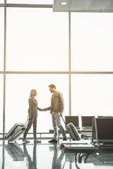 Full length side view smiling girl telling with cheerful man while standing in airport. Happy couple during trip concept