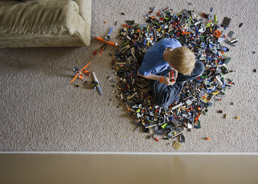 Overhead shot of young blonde boy sitting in a huge lego pile