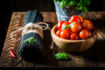 Closeup of black spaghetti with tomatoes and basil