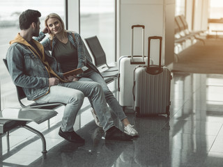 Full length male telling with outgoing girl while they sitting in lounge zone. Positive communication before journey concept