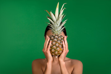 Young girl covering face with pineapple. Her shoulders are naked. Isolated on background