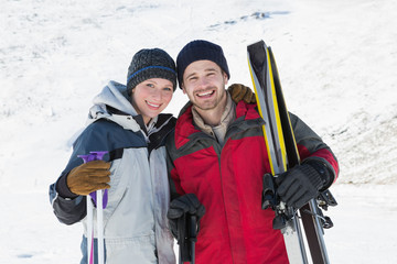 Portrait of a smiling couple with ski boards on snow