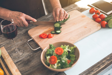 Top view close up of elderly female hands making salad in kitchen. Woman is cutting a cucumber by knife on board