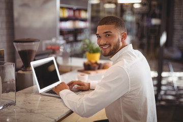 Portrait of smiling young male owner sitting with laptop at counter
