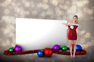 Pretty girl presenting in santa outfit against light glowing dots design pattern